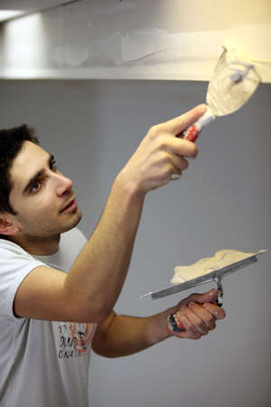 plastering: Decorator carefully plastering roof Stock Photo