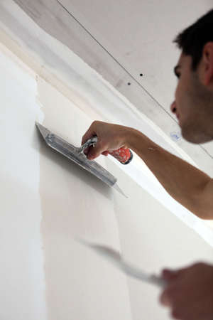 Worker plastering a wall photo