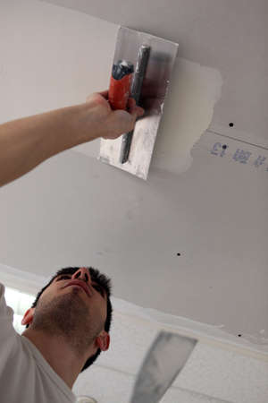 workmanship: Man putting up a plasterboard ceiling