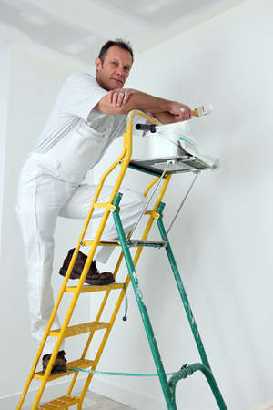 Painter climbing ladder to paint ceiling photo