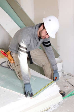 ceiling construction: Man installing wall panels Stock Photo