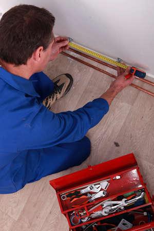 koperen leiding: Loodgieter meten van de lengte van de koperen leiding