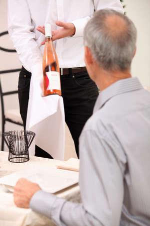 Waiter showing bottle of wine to man dining alone photo