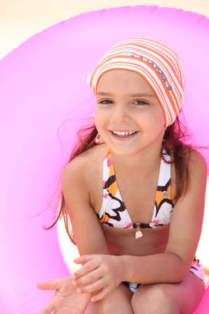 rubber ring: Little girl at the seaside with inflatable rubber ring Stock Photo