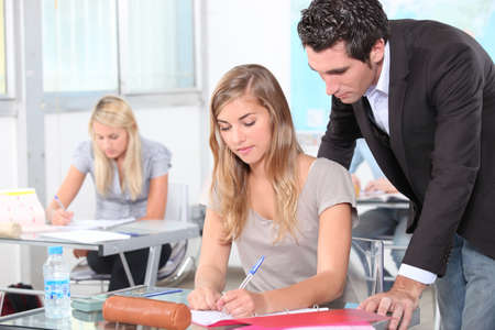 Teacher helping students in the classroom photo