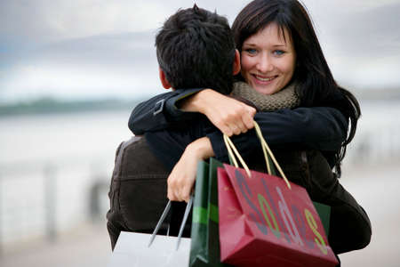 Couple with shopping bags hugging photo