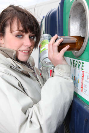 recycling center: Woman recycling glass bottles