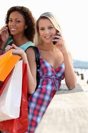mobile telephones: Two friends with shopping bags holding mobile phones
