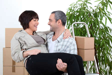unmarried: Man  carrying his partner over the threshold of their new home