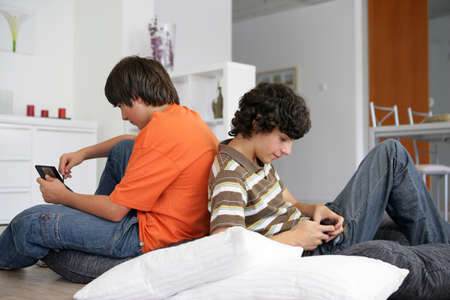 cell phone addiction: Teenage boys with handheld devices