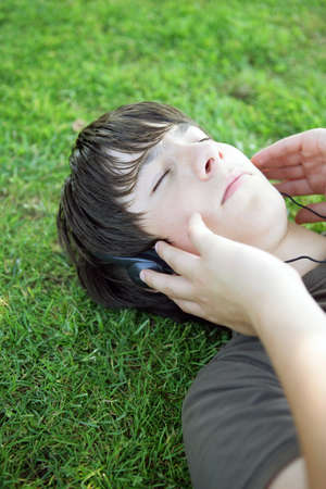 Portrait of a boy listening to music with headphones laid on the grass Stock Photo - 14195243