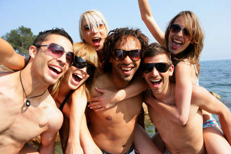 friends party: Group of young adults partying at the beach Stock Photo