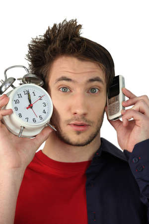 after midnight: Man holding alarm clock and mobile telephone Stock Photo