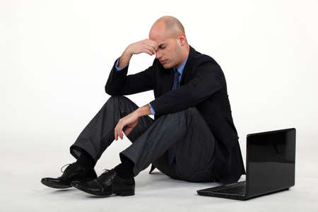 splitting headache: Stressed out businessman with his laptop