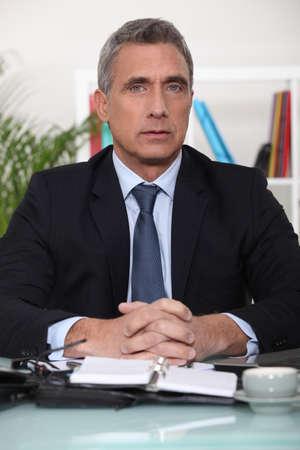 Senior businessman sat at his desk Stock Photo - 14195195