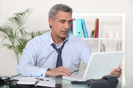 mature businessman working on his desk photo