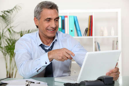 gray haired: Senior businessman pointing at laptop