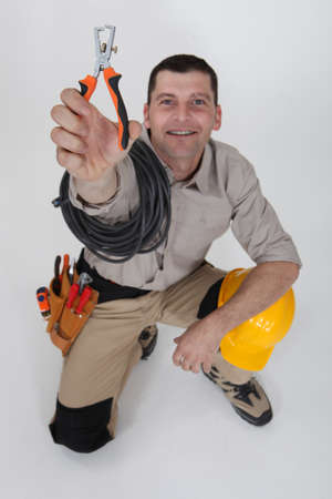 kneeled: An electrician holding a wire stripper.