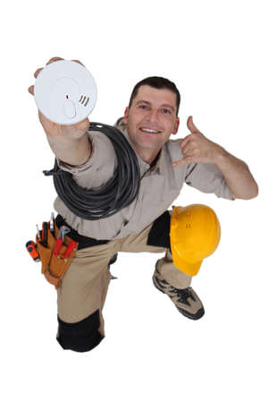 house call: Electrician with a smoke alarm Stock Photo