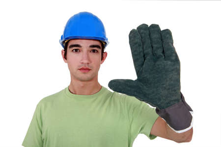 unemotional: Young tradesman wearing an oversized glove Stock Photo