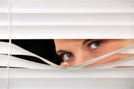 Woman peeking through venetian blinds photo
