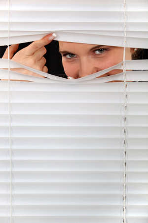 peep: Woman peering through some blinds