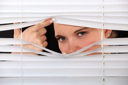 Curious woman peering through window blinds Stock Photo - 14194788