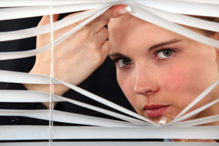 snooping: Woman looking through blinds