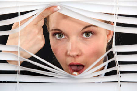 Nosy blond woman peering through blinds photo