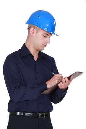 Manual worker filling up a clipboard. Stock Photo - 14194397