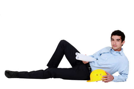 young businessman lying on the floor and holding helmet and blueprint photo