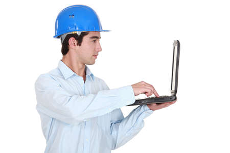 journeyman technician: Man in a hardhat with a laptop Stock Photo