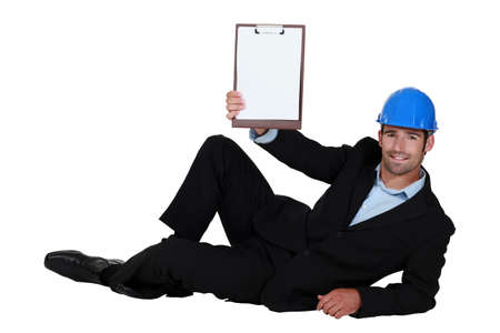 Architect casually laying on floor with clip-board Stock Photo - 14193566