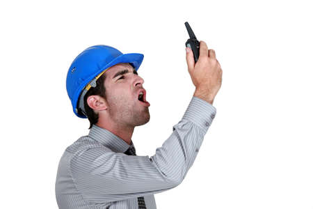 talkie: angry businessman wearing a helmet and shouting on his walkie talkie