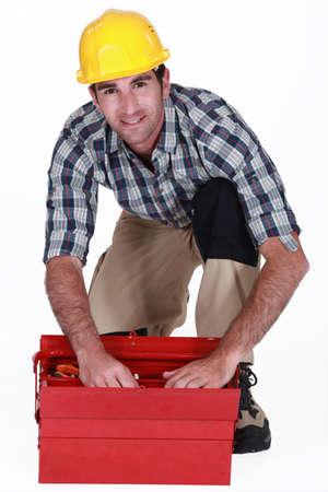 A handyman looking through his toolbox. Stock Photo - 14195272