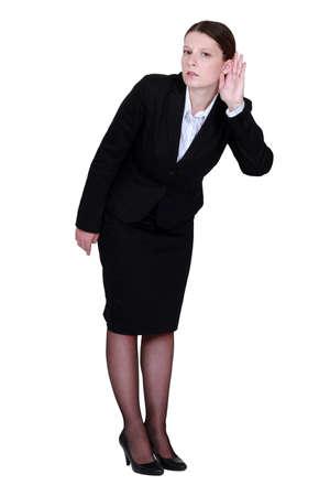 straining: Businesswoman straining her ear