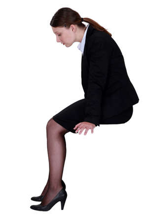 skirt suit: businesswoman sitting in profile with legs dangling Stock Photo