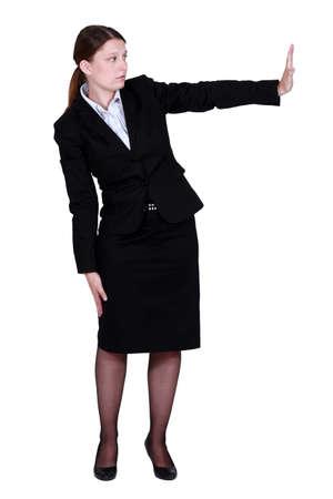 comunicacion no verbal: Empresaria empujando una pared invisible Foto de archivo