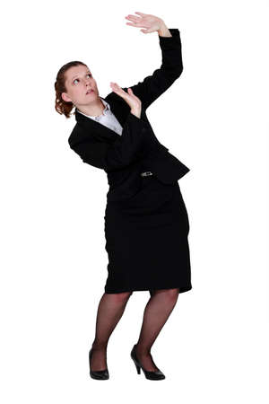 Woman protecting herself with raised hands photo