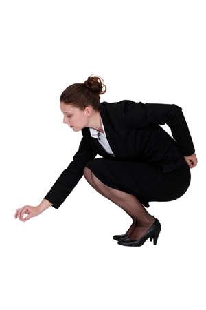 sich b�cken: Gesch�ftsfrau Aufnehmen einer Nadel