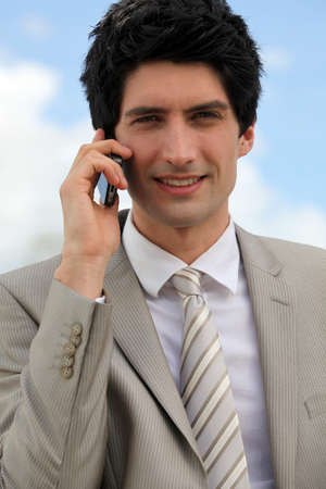 conference call: Businessman making a call outdoors Stock Photo