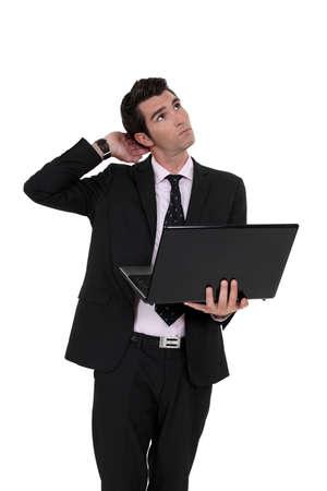 A pensive businessman with a laptop. photo