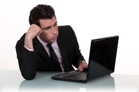 jaded: Annoyed businessman working on his laptop