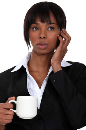 A businesswoman over the phone drinking a coffee. Stock Photo - 14194768