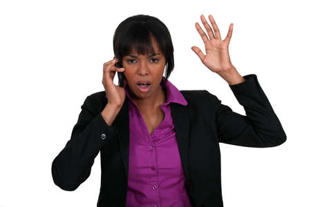 A black businesswoman angry over the phone. photo