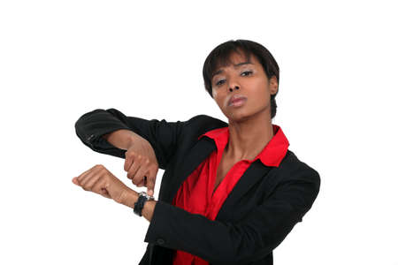 impatient: Businesswoman pointing at her watch