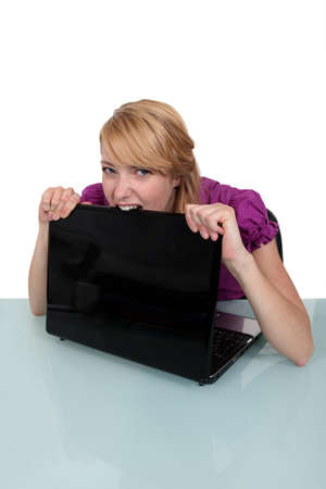 insane insanity: Young woman biting her laptop