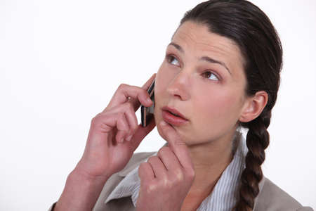 reluctance: Doubtful woman talking on her mobile phone