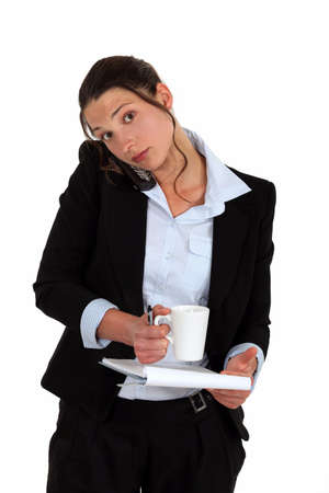 Woman on the phone with notebook and coffee in hand photo
