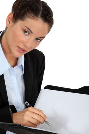 Businesswoman holding pen and folder photo